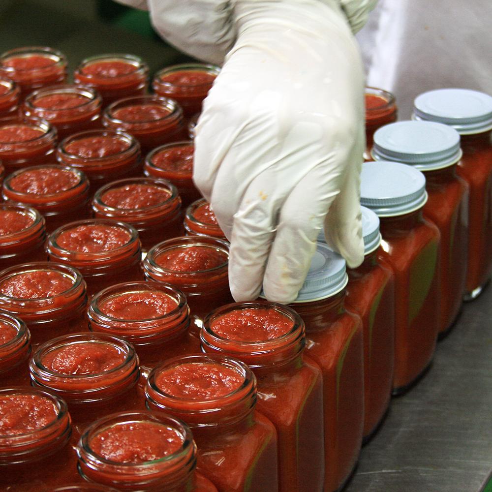 明宝トマトケチャップのできるまで その3  瓶に入れたトマトケチャップを1つずつ丁寧に蓋をしていきます。蓋を付けたトマトケチャップはそのまま高温の熱湯で煮沸されます。